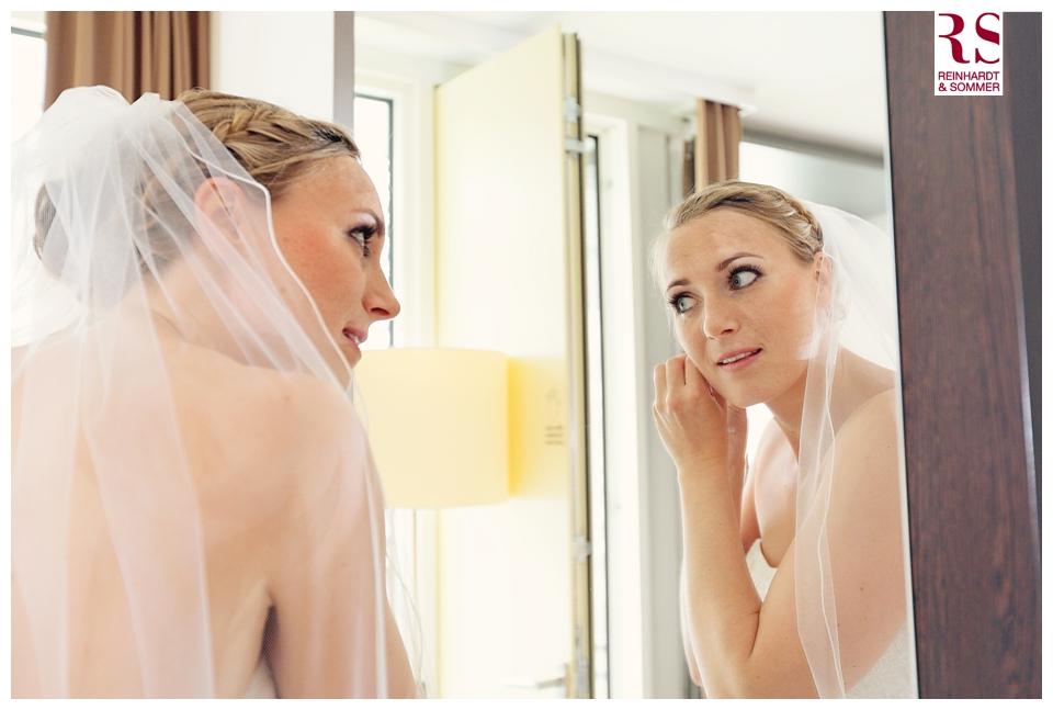 Die Braut bringt ihre Ohrringe an