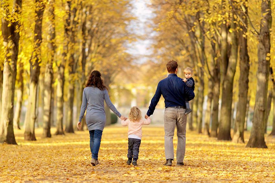 Familie schlendert im Herbst durch einen Park in Potsdam