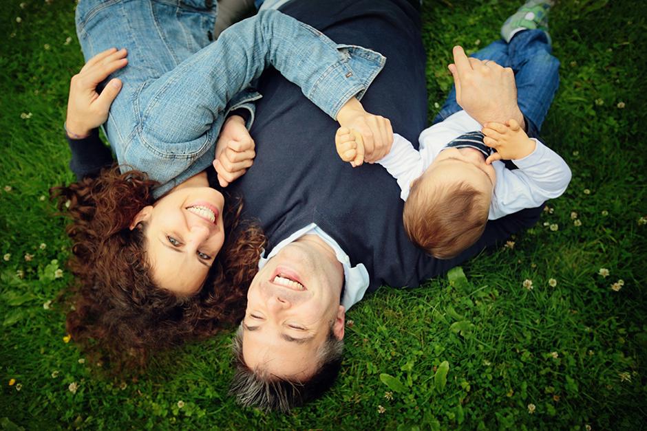Familienfoto lachend auf der Wiese im Schlosspark von Potsdam
