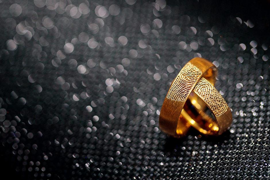 Goldene Trauringe mit Fingerabdruck auf schwarzer Clutch