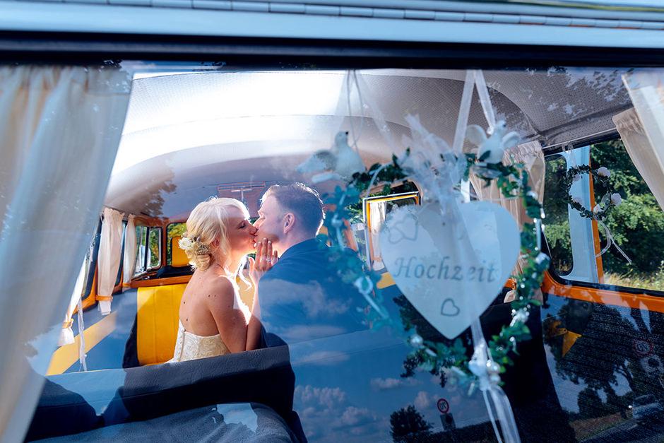 Hochzeitsfoto mit Brautpaar im VW Bulli