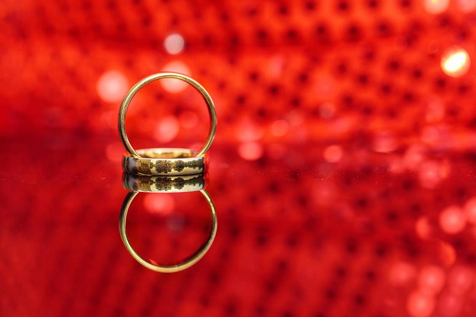 Goldene Trauringe aus Potsdam vor rotem Hintergrund