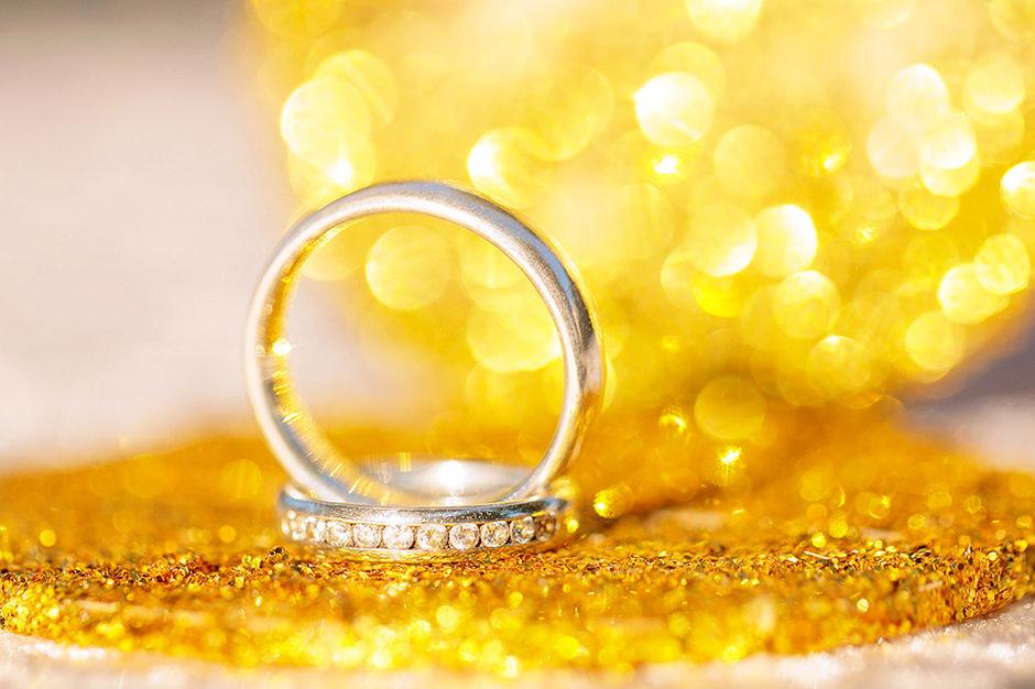 Trauringe vor gold funkelndem Hintergrund
