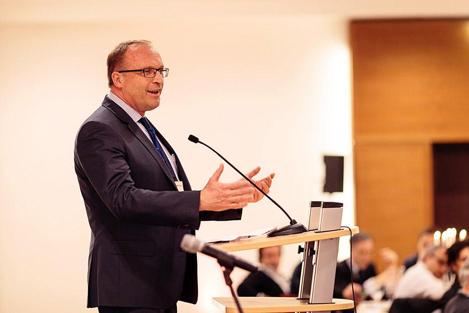 Foto mit Redner auf einer Bühne bei einer Tagung