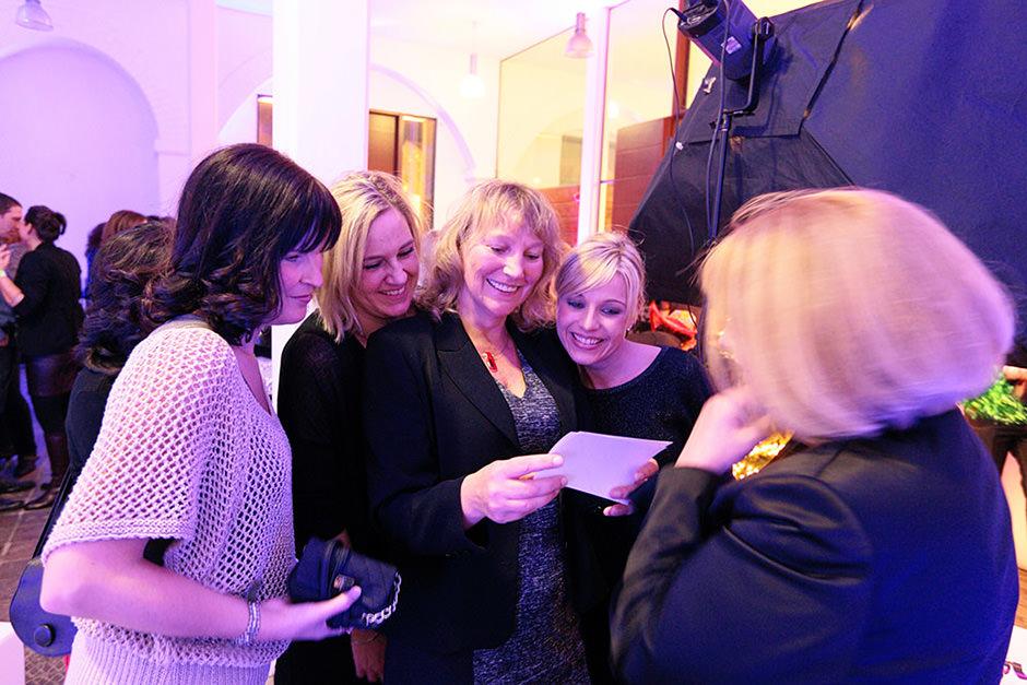 Gäste einer Veranstaltung erfreuen sich an Fotodrucken