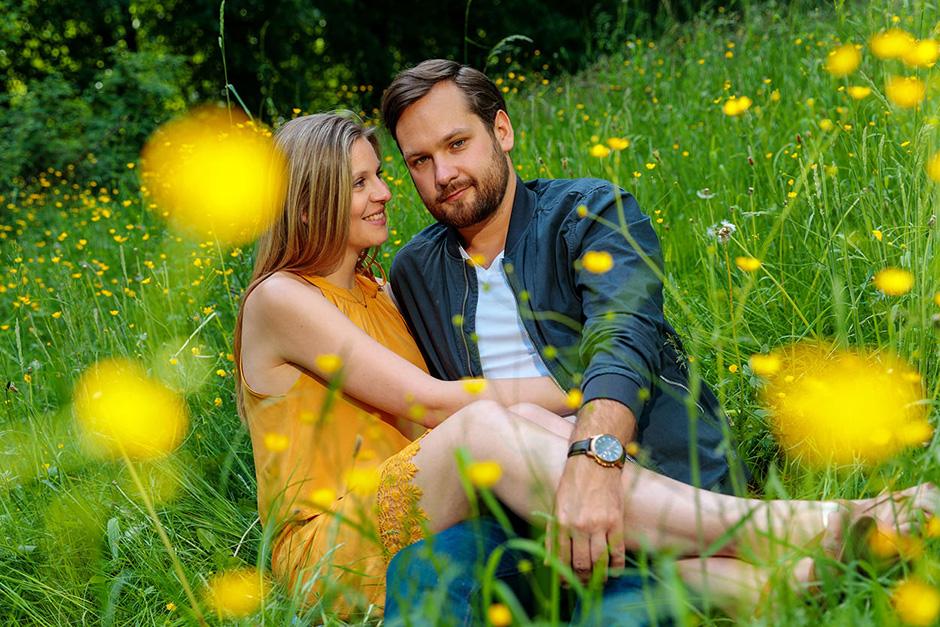 verlobtes Paar sitzt bei der Orangerie Potsdam im Gras
