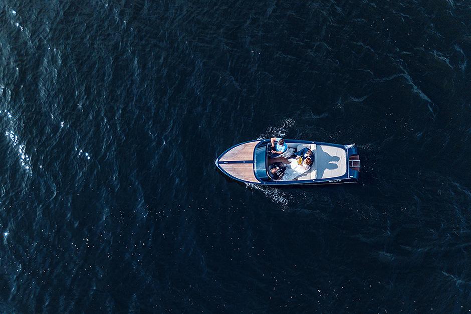 Drohnenfoto eines Hochzeitspaares im Boot nach der Trauung