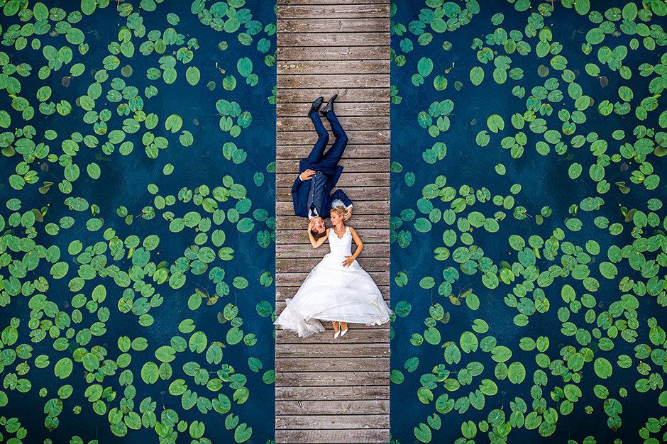 Von Seerosen umgebenes Brautpaar liegt auf einem Steg in Brandenburg