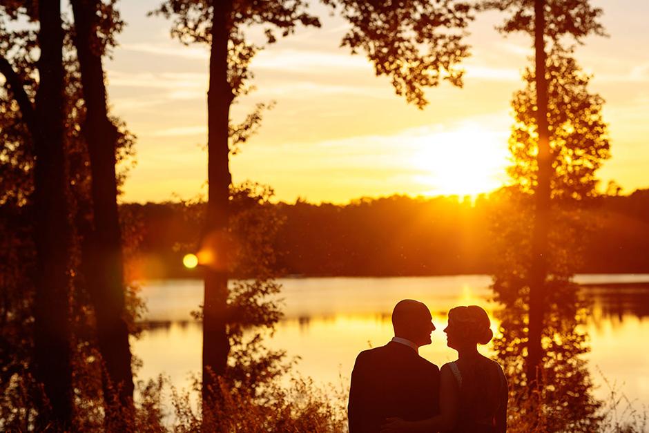 Hochzeitsfoto mit Silhouette vom Brautpaar am See in Brandenburg im gelb leuchtenden Abendlicht