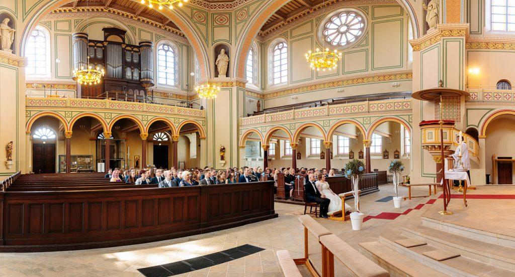 Ein Blick auf das Brautpaar, die Gäste und das Innere der Peter und Paul Kirche Potsdam während der Trauung