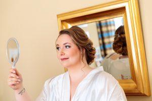 Auch die Braut wirft einen prüfenden Blick in den Spiegel nach dem Brautstyling in den Räumlichkeiten des Inselhotels Potsdam