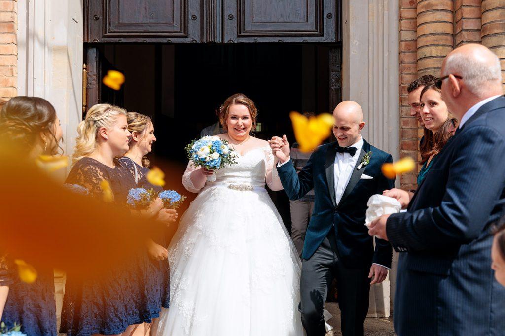 Das Brautpaar wird von seinen Gästen vor der Peter und Paul Kirche bejubelt