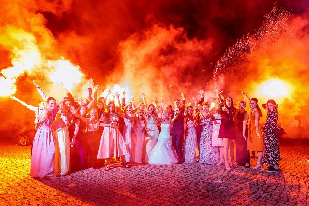 Sektexplosion und Brautpaar unter Bengalofeuer