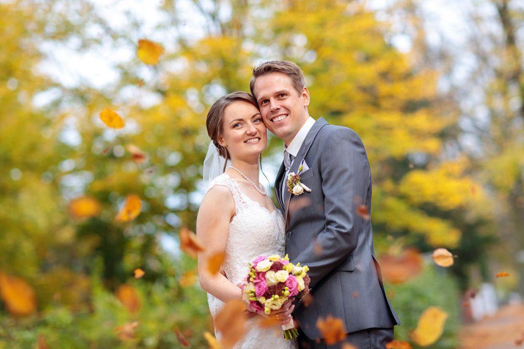 Brautpaar mit farbenfrohen Blättern im Herbst