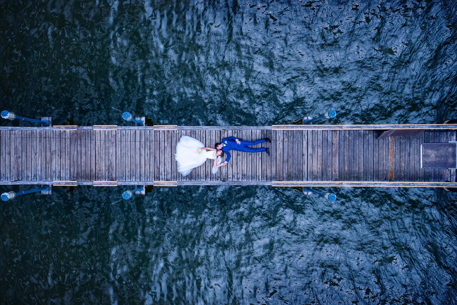Hochzeitsfoto in Neuruppin mit Drohne fotografiertes Brautpaar auf Steg zum Ruppiner See