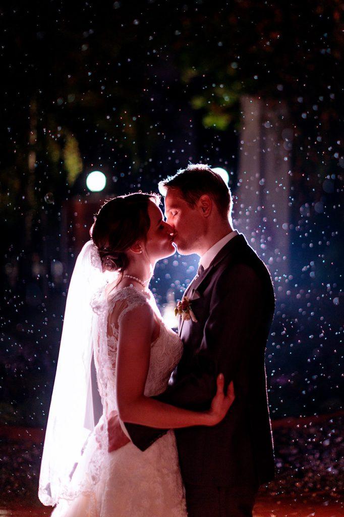 Ein Brautpaar im Regen am Abend