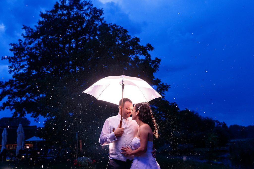 Ein Brautpaar kuschelt unter einem Regenschirm im Spreewald