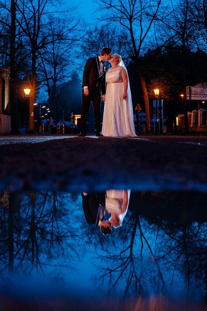 Brautpaar spiegelt sich in den Pfützen nach einem Regenschauer in Berlin