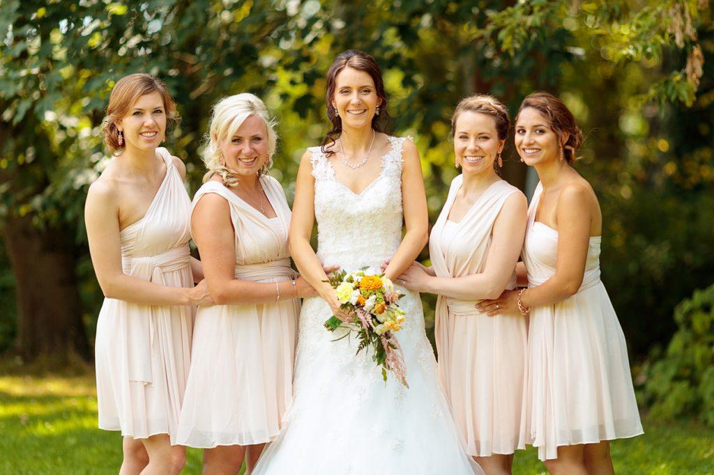 Die Braut mit ihren Brautjungfern in cremefarbenen Outfits