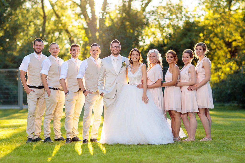 Braut und Bräutigam mit Freunden in cremefarbenen Outfits