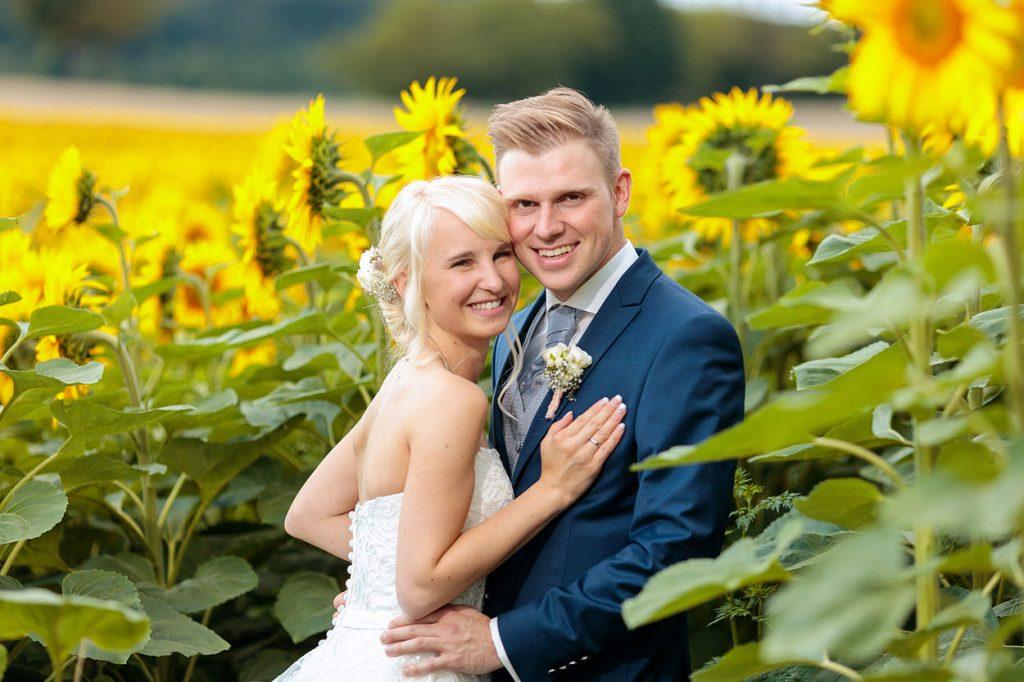 Ein Brautpaar im Sonnenblumenfeld in Beelitz