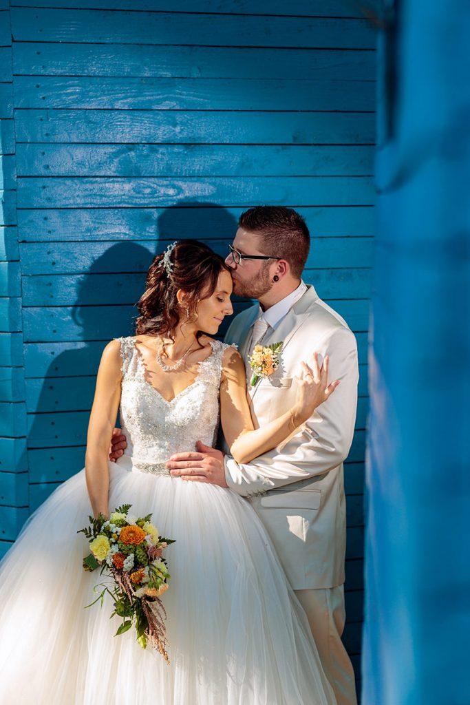 Ein Brautpaar vor einer leuchtend blauen Holzwand im Sommer