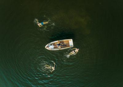 Hochzeitspaar im Boot umgeben von Schwimmern