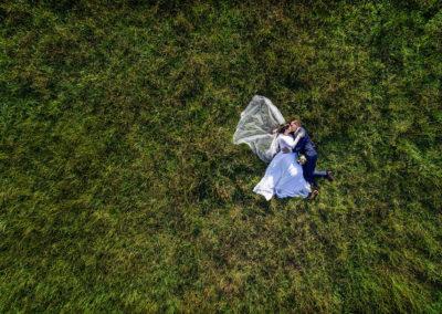 Hochzeitspaar im Gras liegend mit Drohne fotografiert