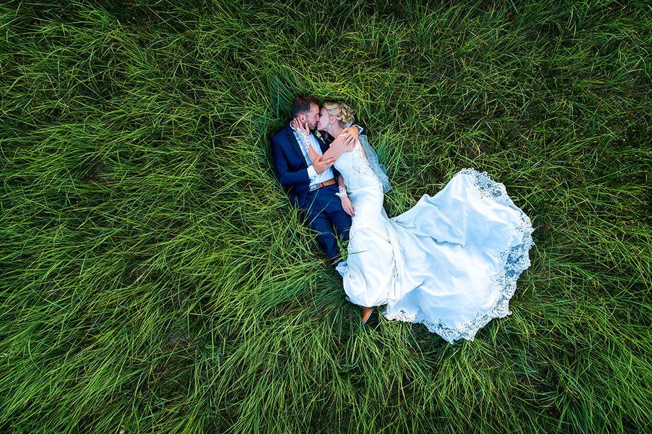 Ein im Gras liegendes Brautpaar in einem Drohnenfoto von Hochzeitsfotograf