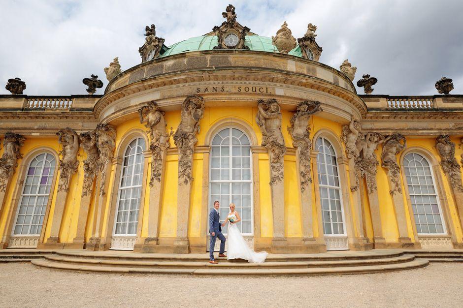 Hochzeitsfoto mit Hochzeitspaar vor Schloss Sanssouci Potsdam