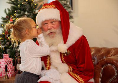 Mädchen flüstert dem Weihnachtsmann ins Ohr