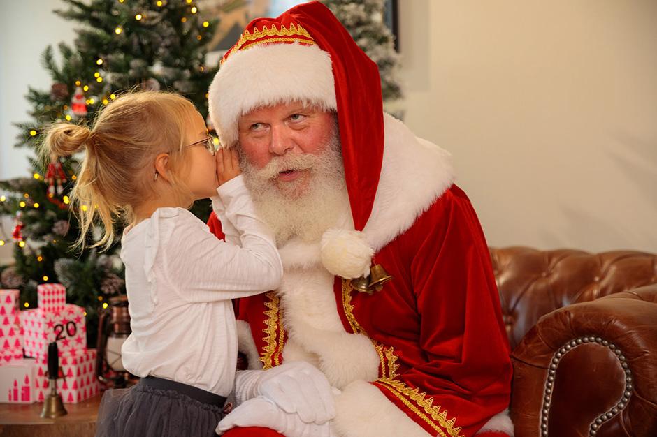 Ein Mädchen flüstert dem Weihnachtsmann beim Fotoshooting in Potsdam ihre Wunschliste ins Ohr.