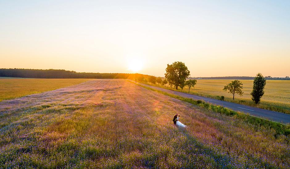 Hochzeitsfoto mit Drohne: Brautpaar im Sonnenuntergang auf Feld in Brandenburg