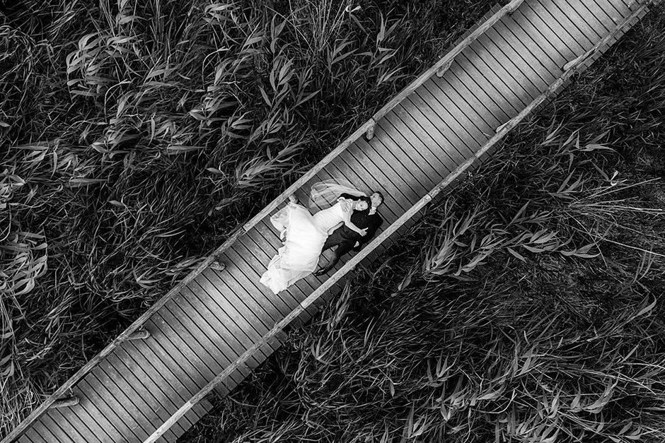 Drohnenfoto von einem Hochzeitsfotograf auf einer Hochzeit: Brautpaar liegt auf Steg