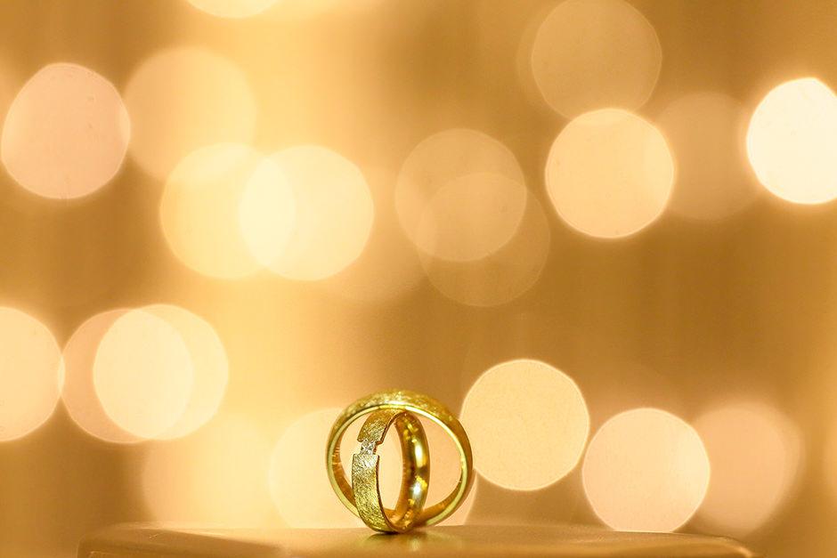 Goldene Trauringe mit leuchtendem Bokeh