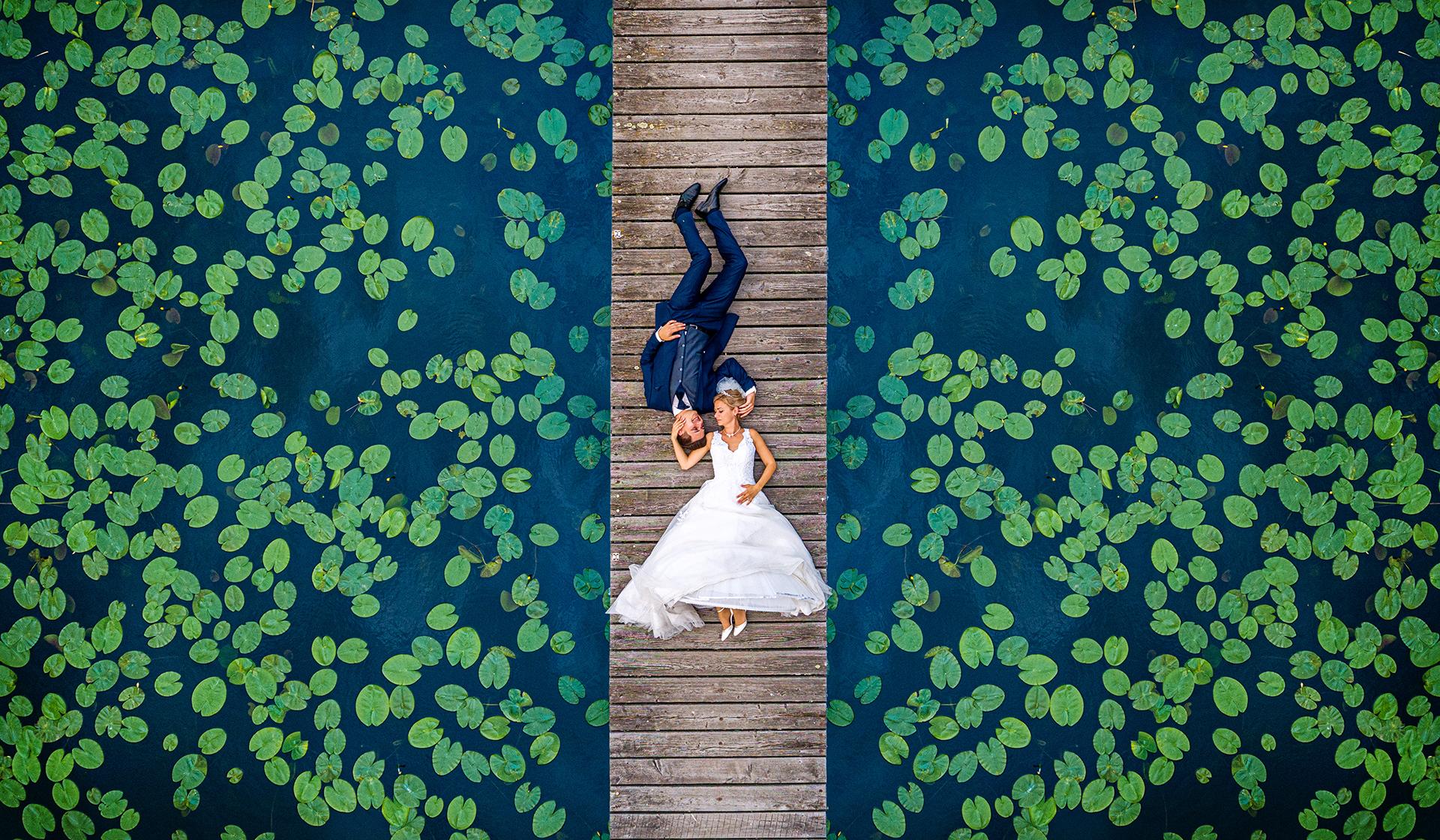 Ein Brautpaar liegt auf einem Steg und ist von Seerosen umgeben