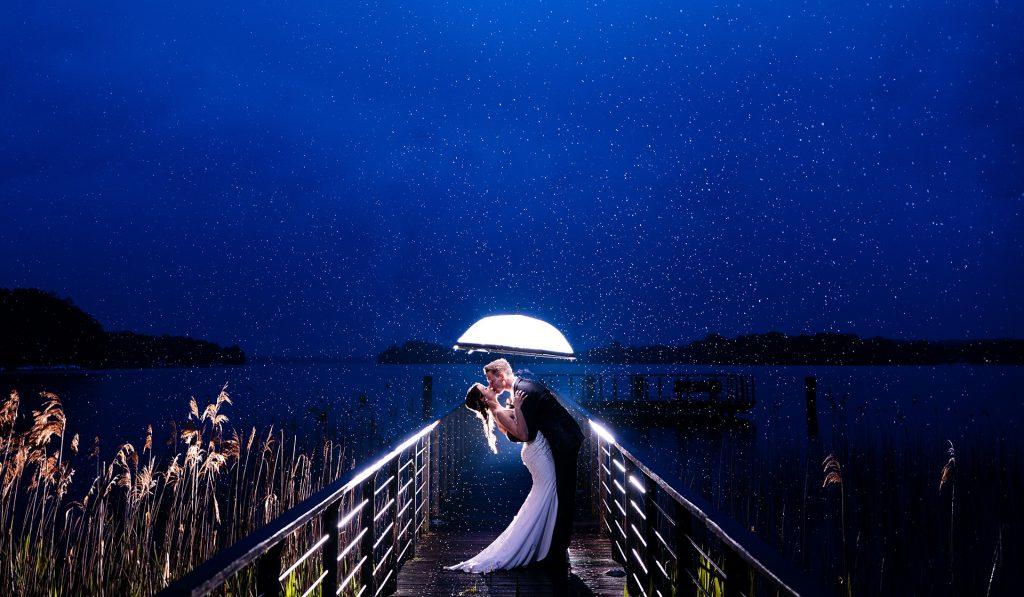 Hochzeitsfoto mit Brautpaar im Regen auf einem Steg in Brandenburg Bad Saarow