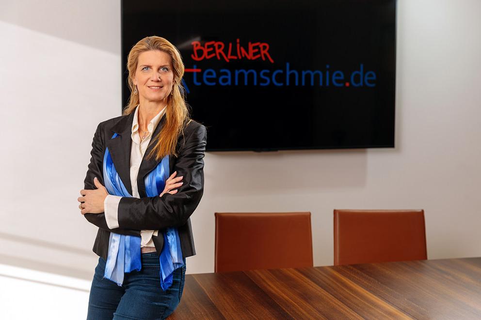 Geschäftsfrau schaut auf Foto im Konferenzraum in Potsdam überzeugt
