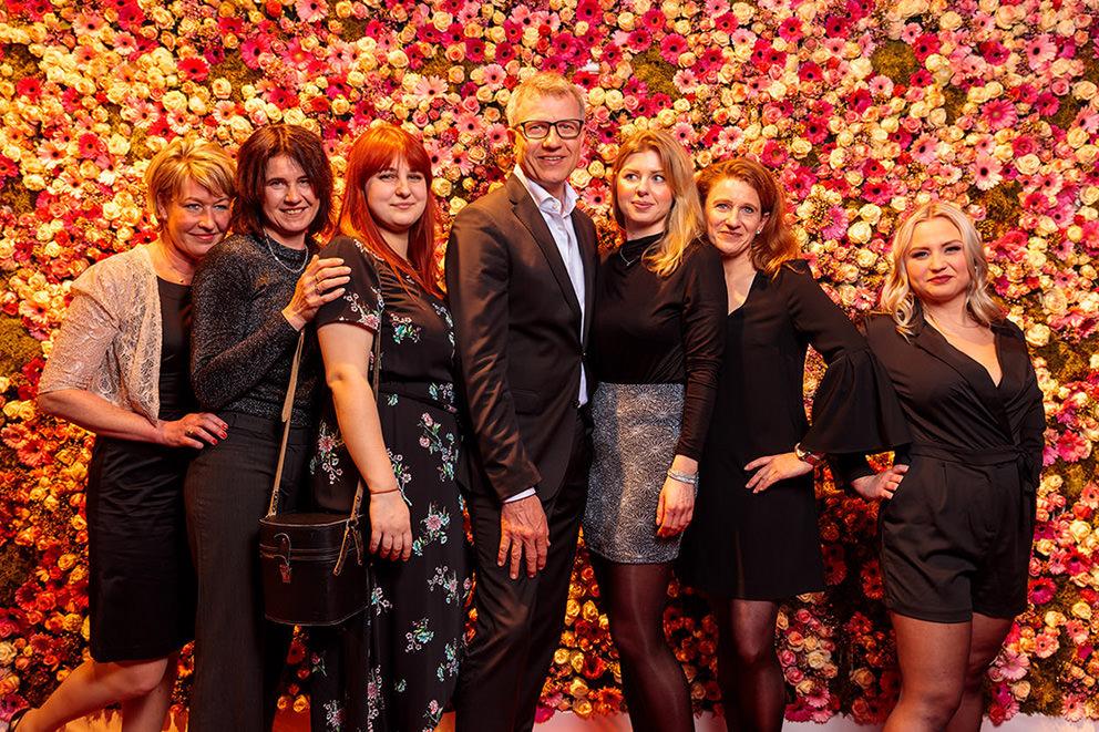 Teamfoto auf Abendevent vor schöner Blumenwand