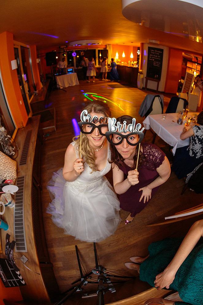Braut macht Foto mit Trauzeugin vor Selfiebox