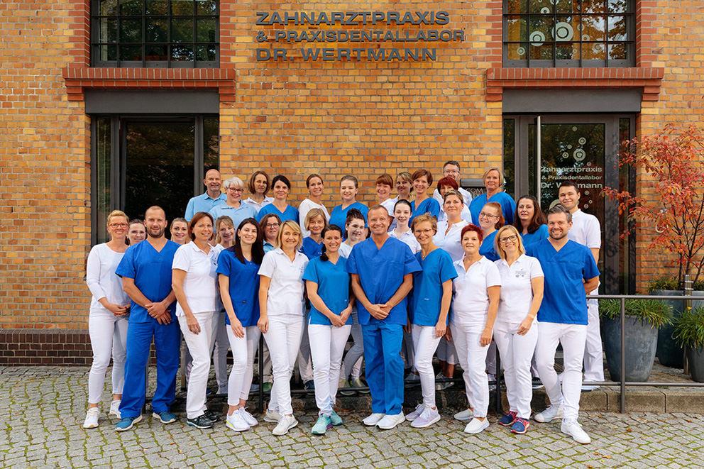 Gruppenfoto von Zahnarztpraxis mit großem Team alle lachen in Potsdam