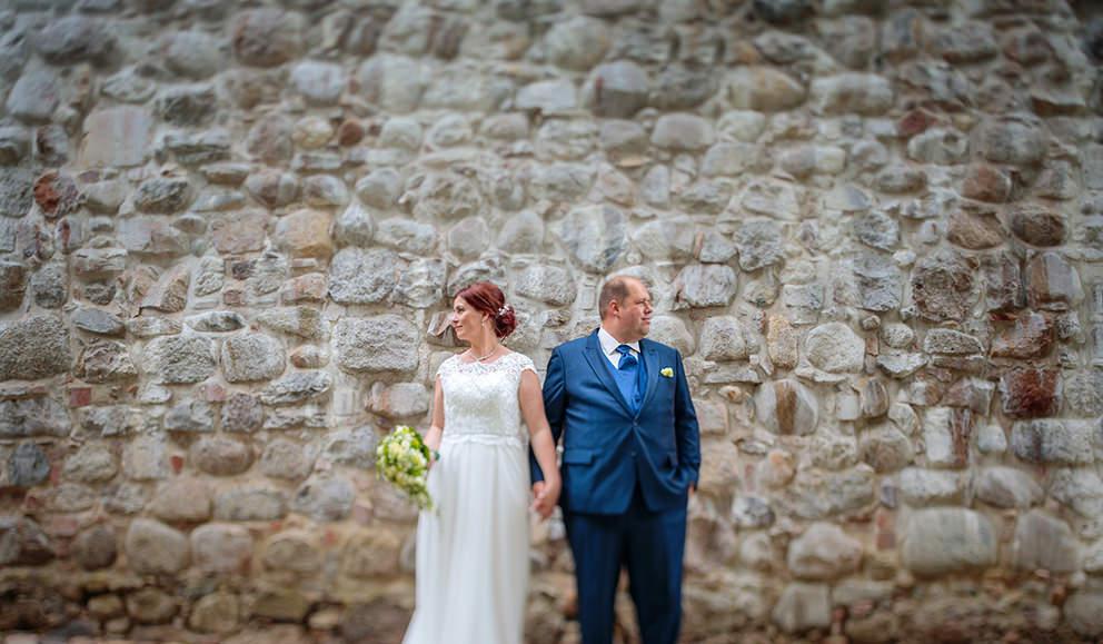 Hochzeitsbild vor einer stilvollen Steinwand
