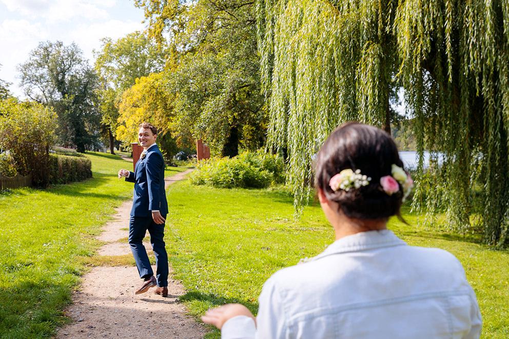 Bräutigam winkt seiner Braut vor Trauung