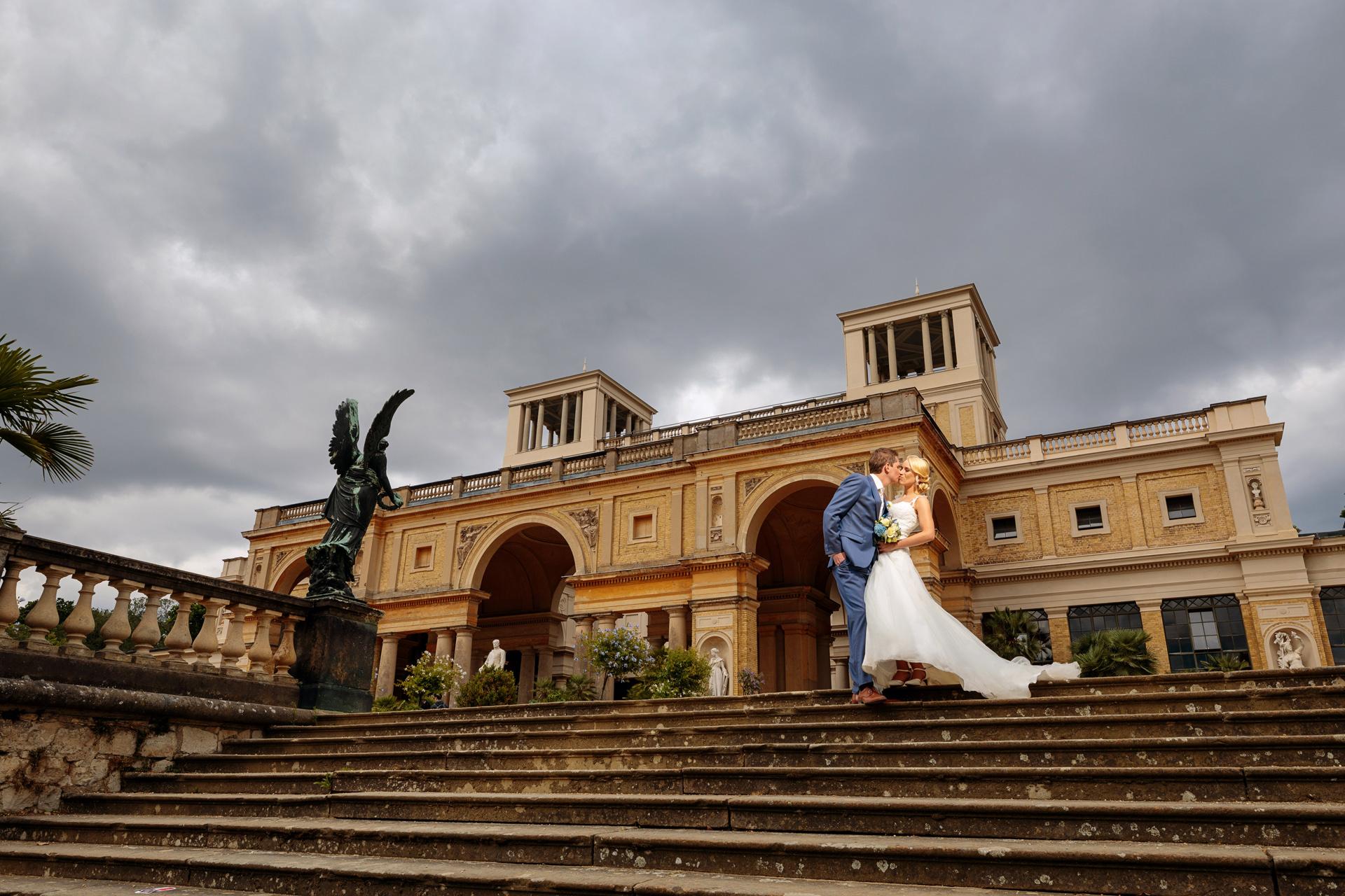 Hochzeitsfotograf fotografiert Brautpaar vor Orangerie am Tag der Hochzeit in Potsdam