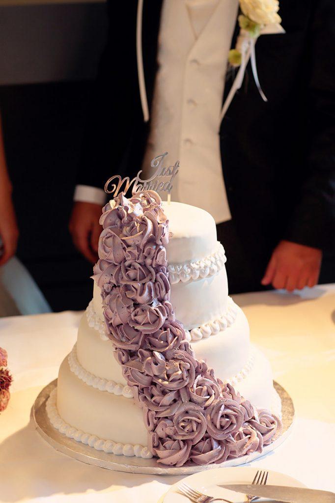 Die Hochzeitstorte mit lila Blumen und einem Just-Married Topping