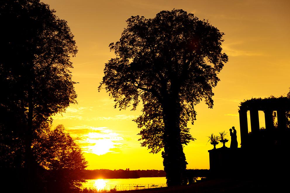 Silhouette eines Brautpaares im Sonnenuntergang am Schloss Glienicke in Berlin