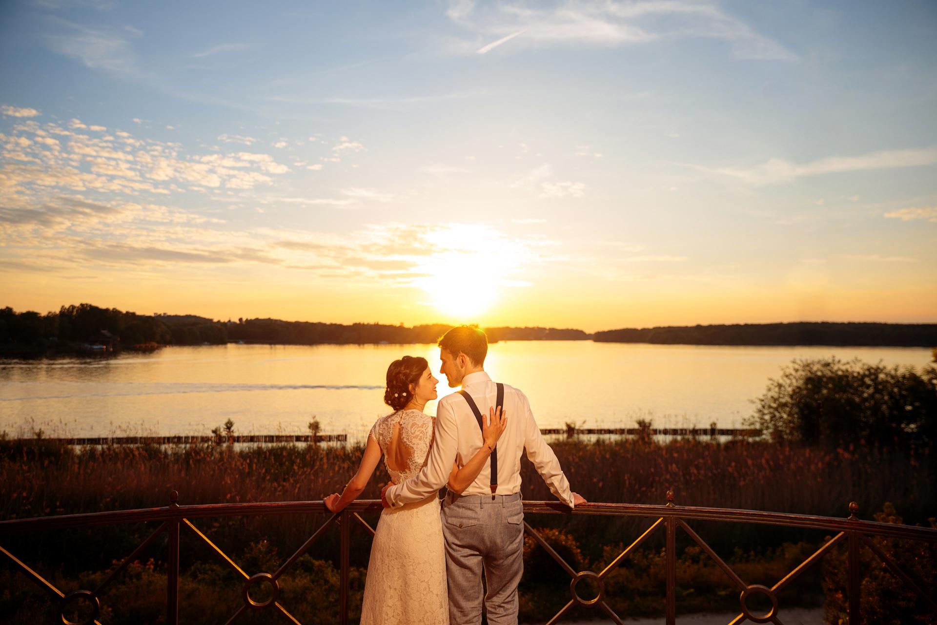Brautpaar blickt sich im Abendhimmel über dem See in Berlin an.