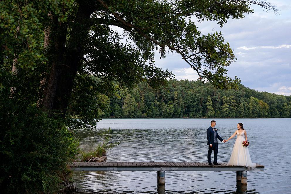 Auf einem Steg in Schorfheide steht ein Brautpaar