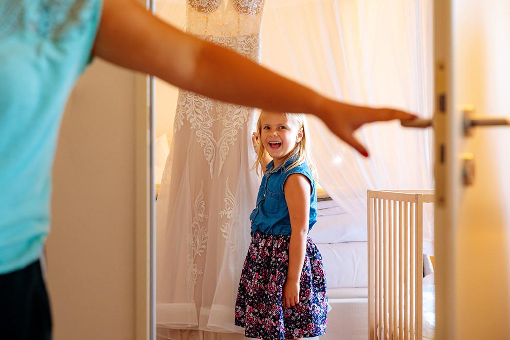 Kleines Blumenmädchen betrachtet begeistert das Brautkleid