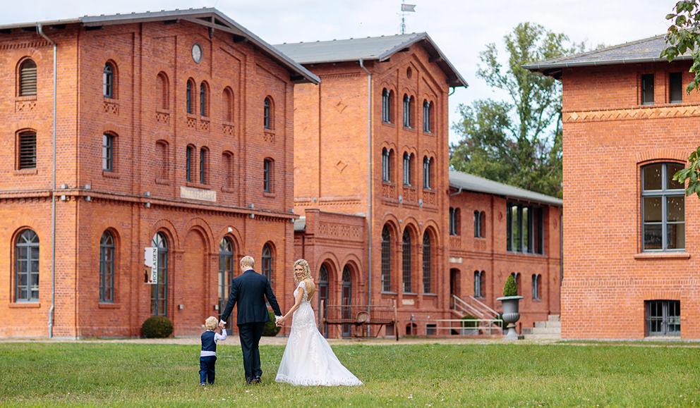Brautpaar spaziert mit Kind über das Landgut Stober in Nauen